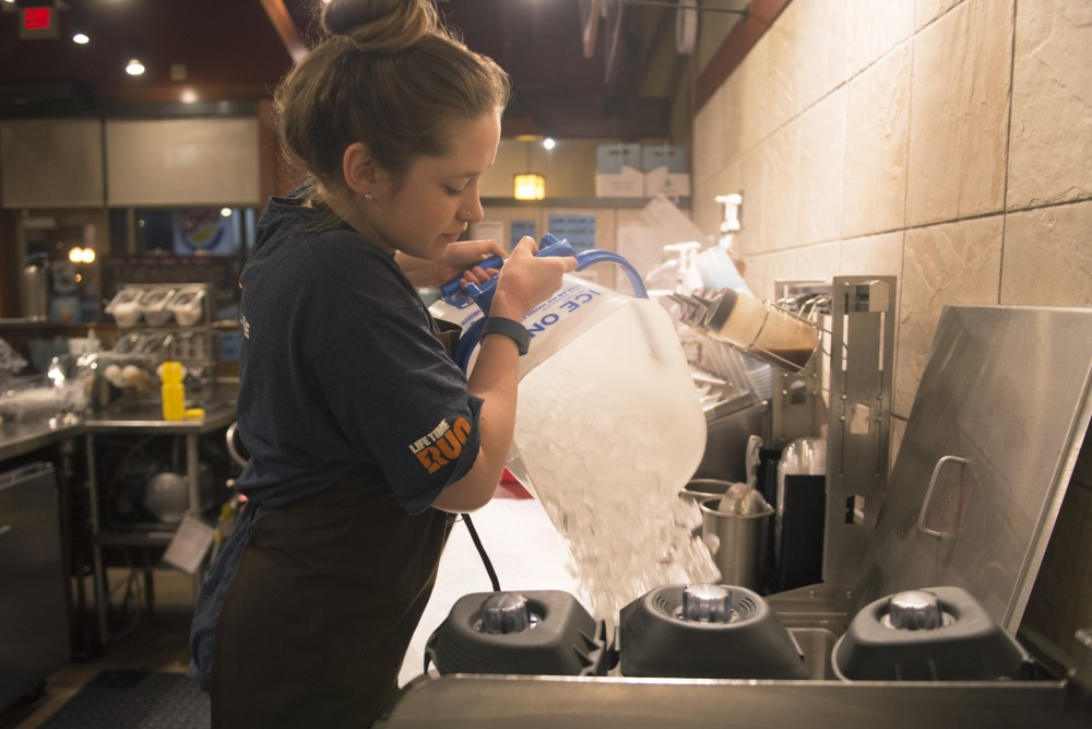 Senior Meredith Campbell fills up the cooler with ice in Caribou Coffee in Stadium Village before opening.