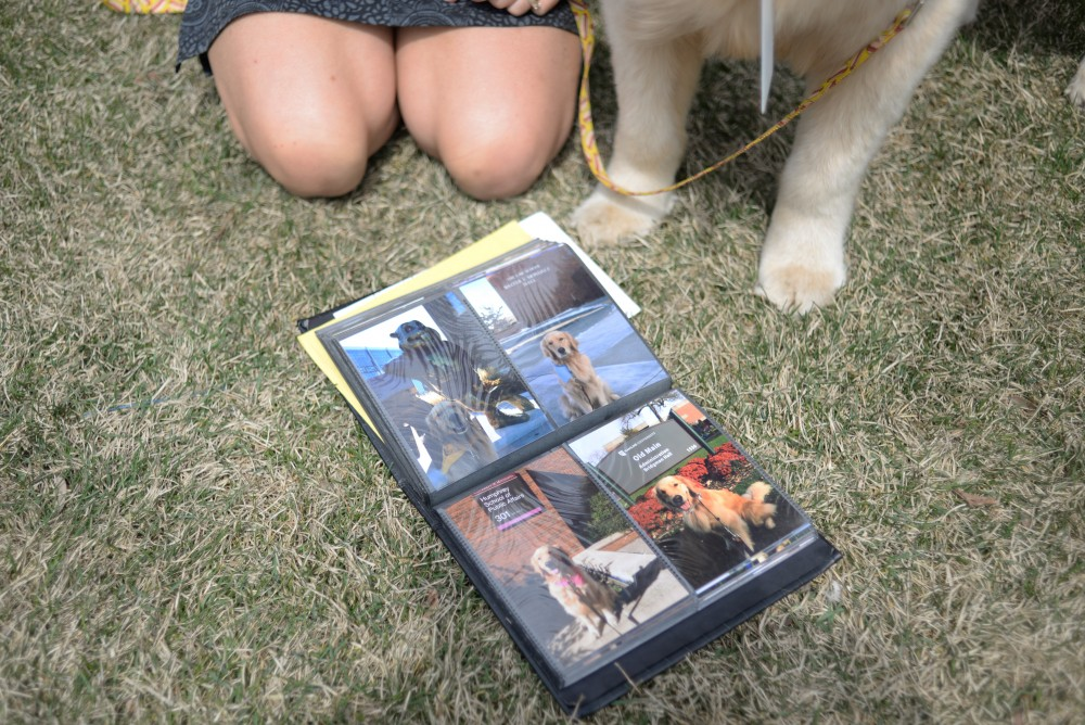 Holly Parker shows a photo album of places Bailey the golden retriever has visited outside of the Masonic Children's Hospital on Tuesday, May 1.