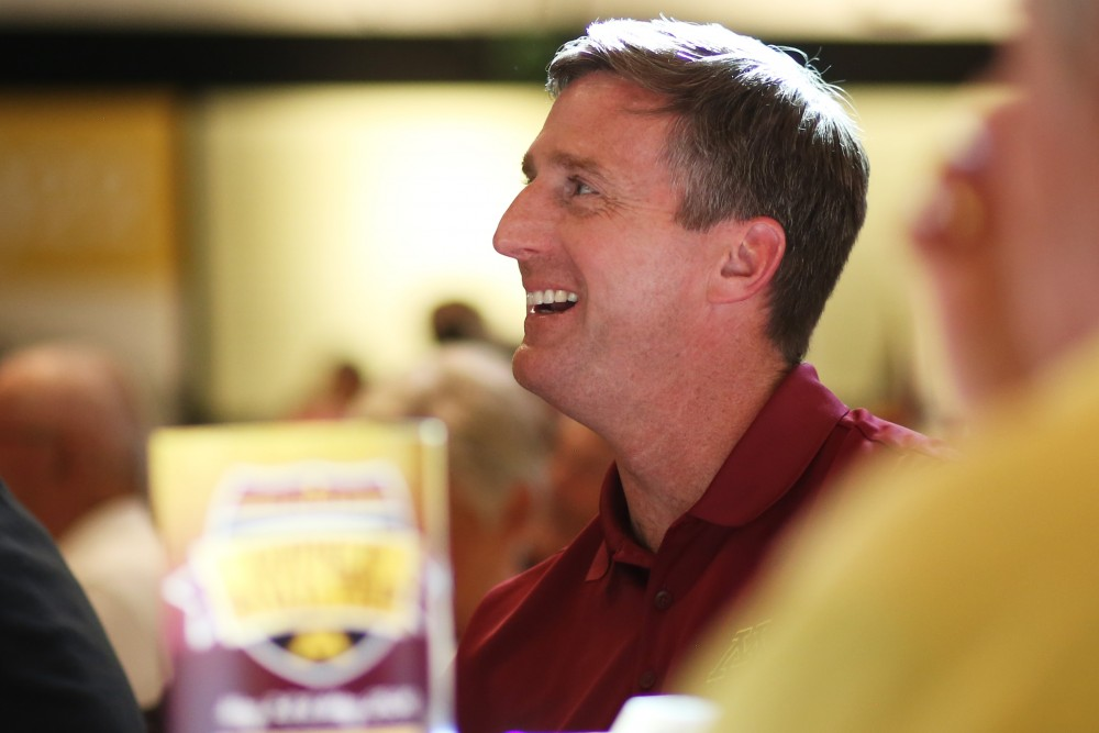 Athletic Director Mark Coyle listens to coach John Carlson speak during the Gopher Road Trip on Thursday, May 24, 2018 in Alexandria, Minnesota.