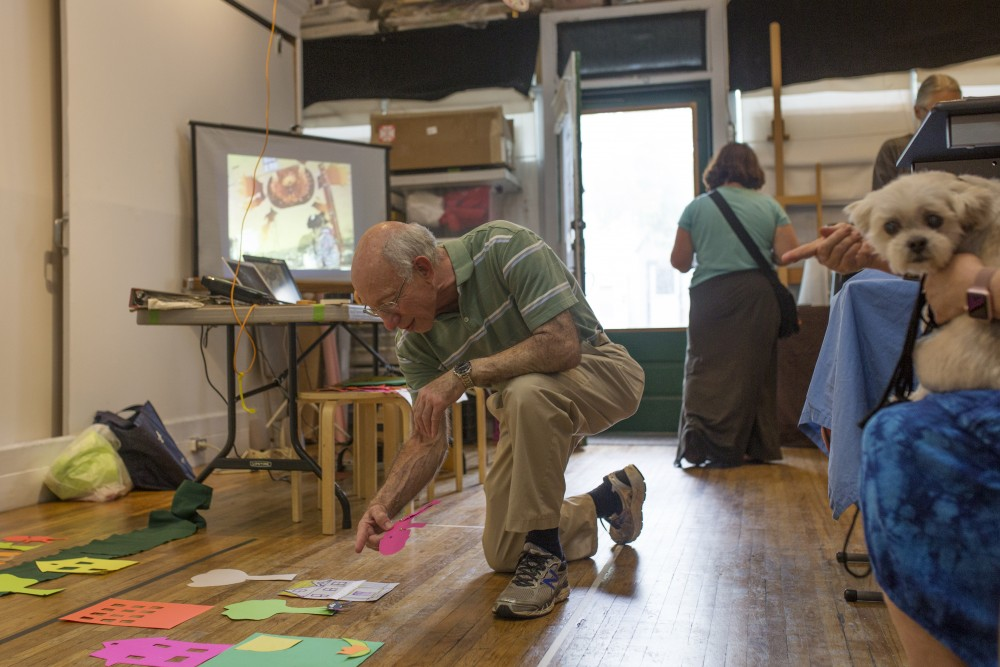 Michigan native Jacob Weintraub places a cut-out paper person onto John Akre's two-day ongoing animation project on Saturday, June 16.