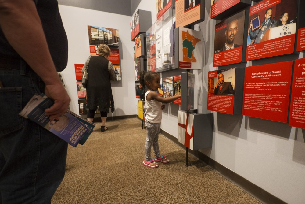 Rahma Osman, 3, spins an informational block at the History Center's new