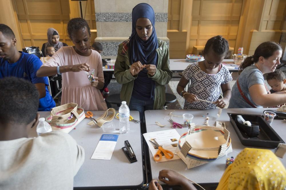 Nasram Qasim, left, Nasra Qasim and Hana Qasim weave traditional Somali baskets at the History Center's new