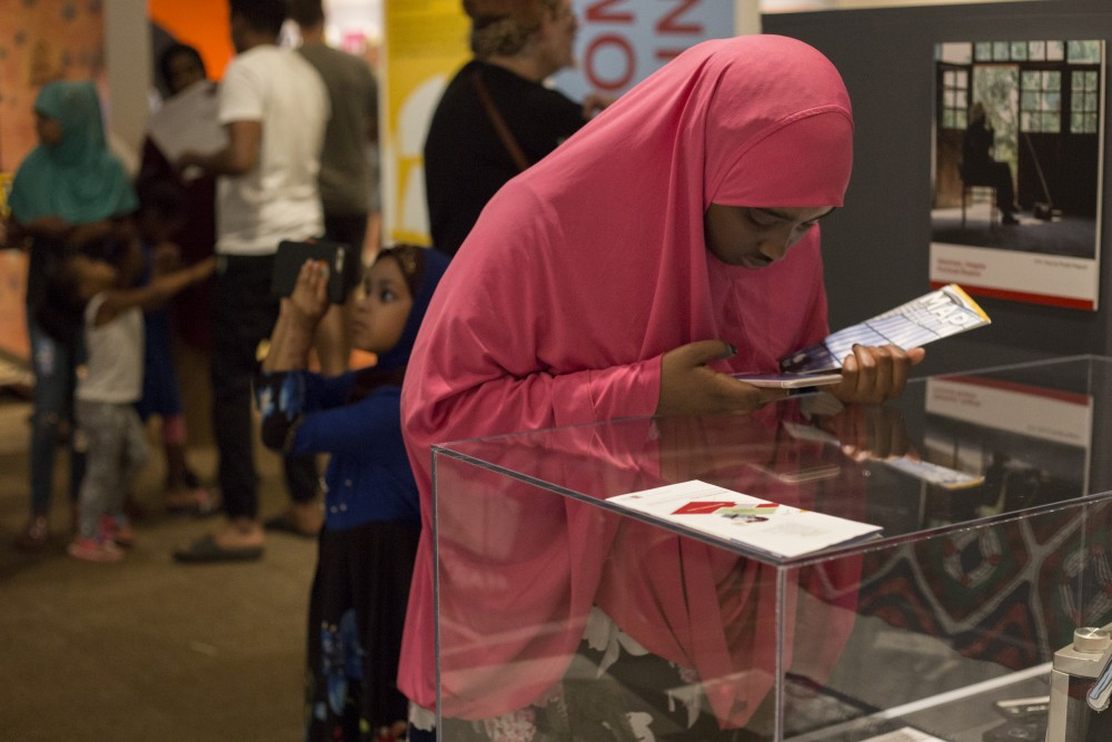 Sundus Osman takes a photo of a radio on display at the History Center's new