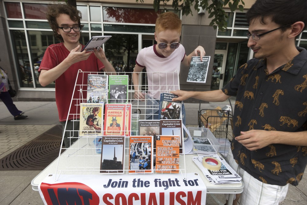 Max Halpern Madelyn Huhta and Arman Ebrahimi set up an information station for the International Marxist Tendency at the