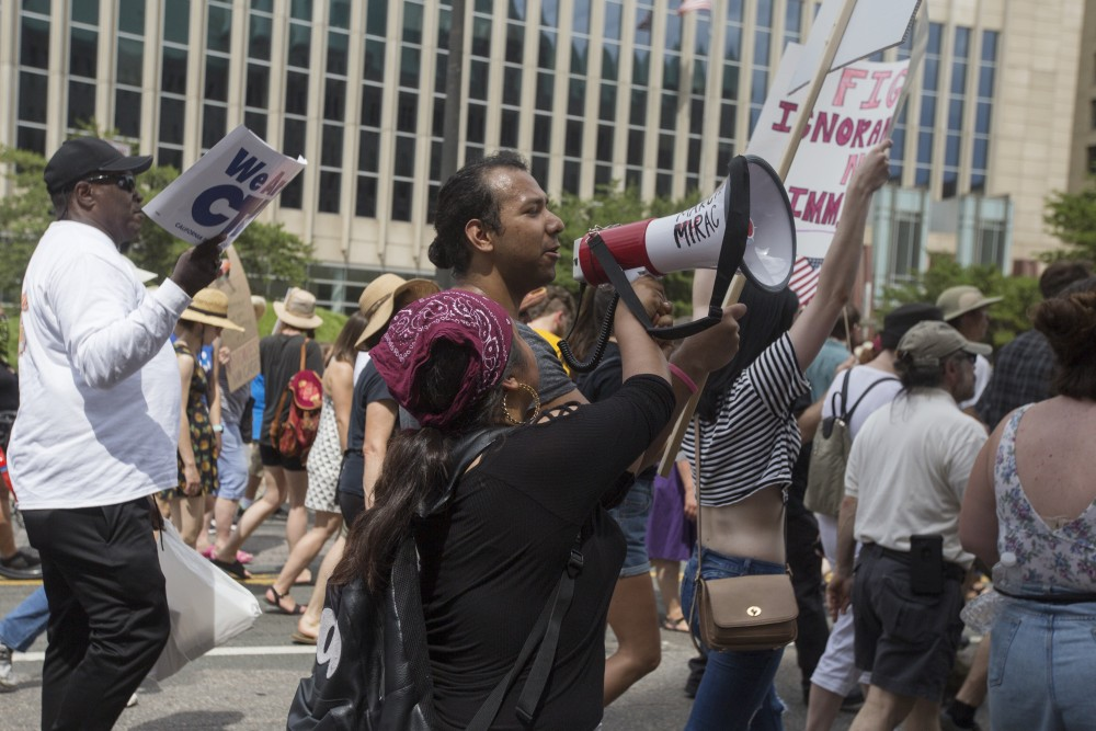 A member of Minnesota Immigrant Rights Action Committee passes the megaphone to another marcher at the