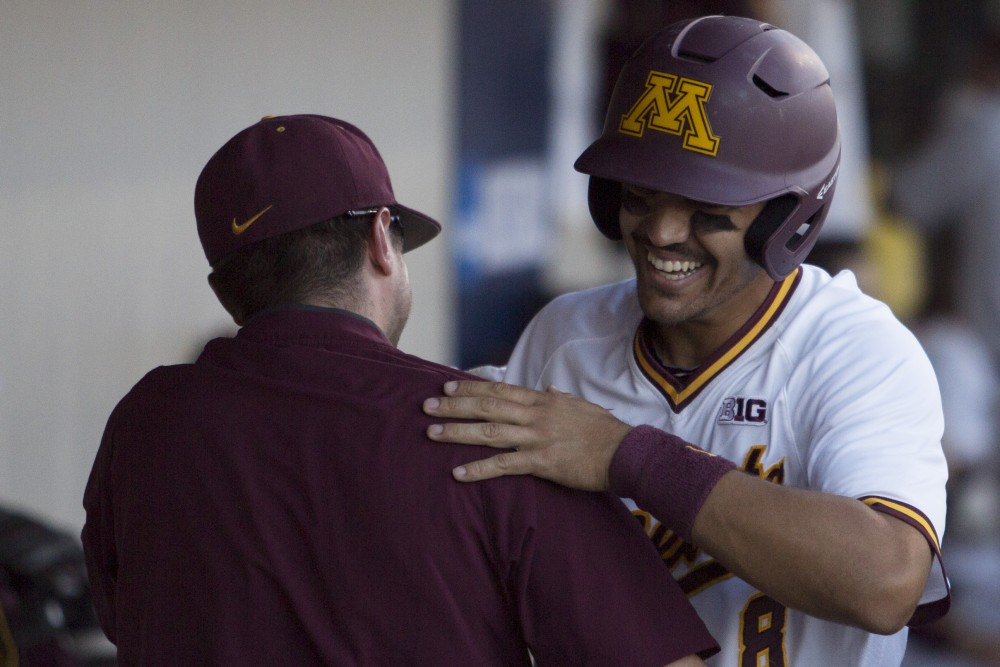 Infielder Micah Coffey hugs his coach after scoring a run during the game against Canisius on Friday, June 1, 2018 at Siebert Field. The Gophers beat Canisius 10-1.
