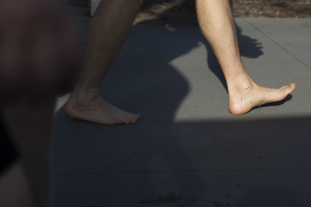 A festival-goer walks barefoot through the grounds of Rock the Garden on Saturday, June 16.