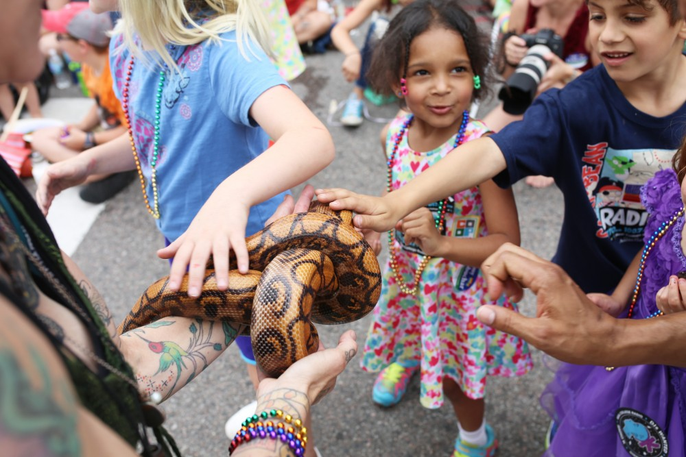 Kids run into the street to pet a snake during the 2018 Twin Cities Pride parade on Sunday, June 24.