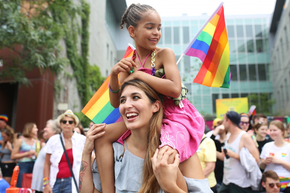 <p>Natalie Deeble and daughter Saniya watch as the Pride Parade marches down Hennepin Ave in Minneapolis on June 24, 2018.</p>
