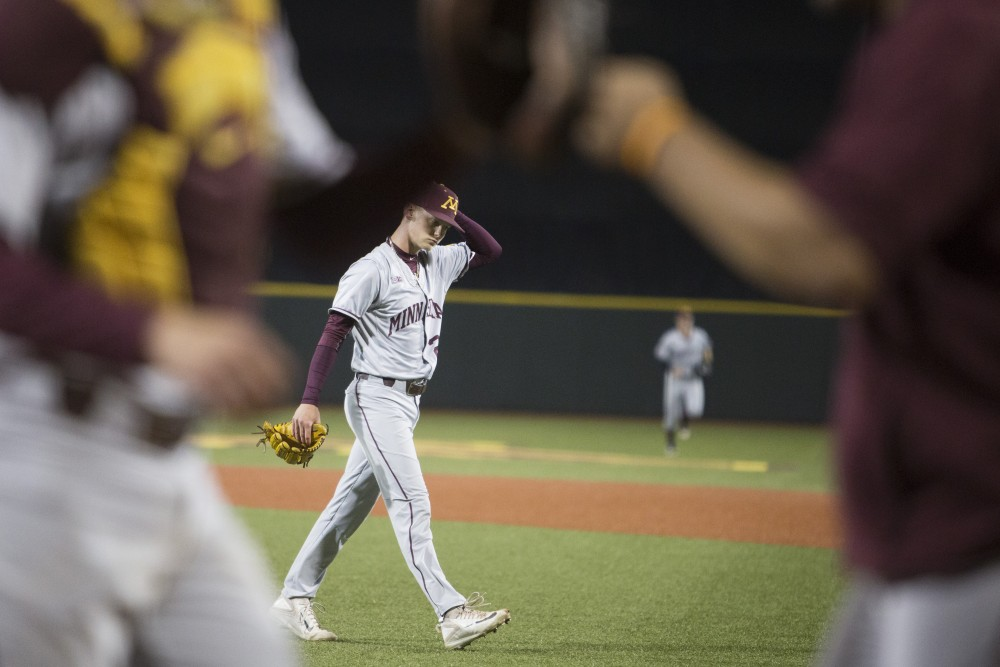 Pitcher Max Meyer walks off the field as his teammates fist bump to his successful inning during the game against UCLA on Saturday, June 2, 2018 at Siebert Field. The Gophers won 3-2.