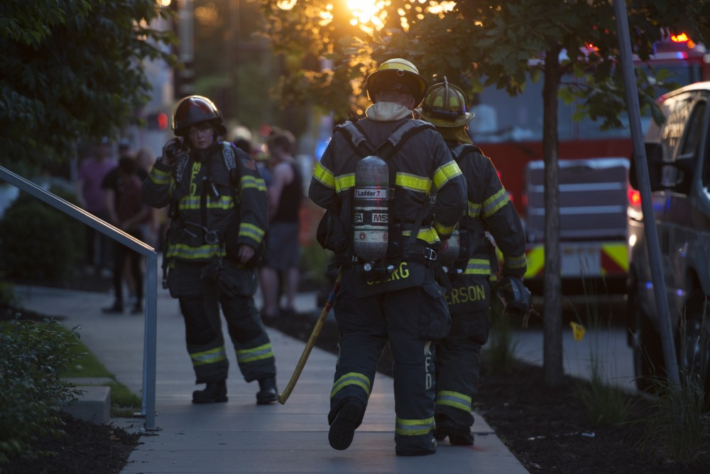 Members of the Minneapolis Fire Department communicate outside FloCo Fusion Apartments after a carbon monoxide leak forced residents outside.