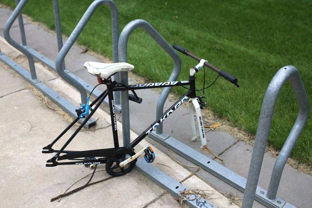 A bike with its wheels stolen sits locked outside of Coffman Memorial Union.