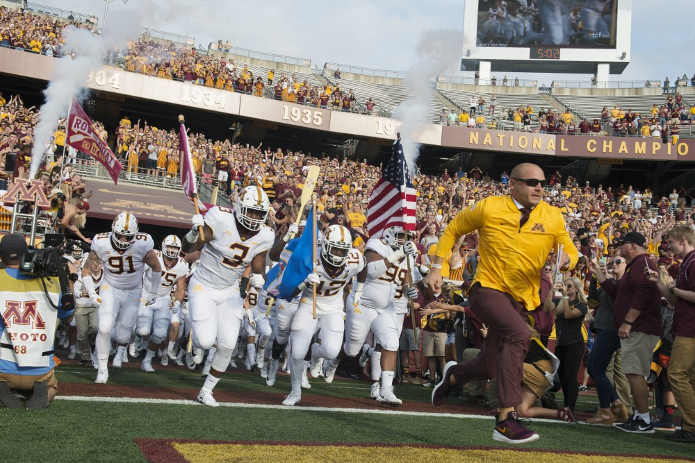 Head coach P.J. Fleck and the Gophers run onto the field before their season opener at TCF Bank Stadium on Thursday, Aug. 30. The Gophers defeated the New Mexico State Aggies 48-10.