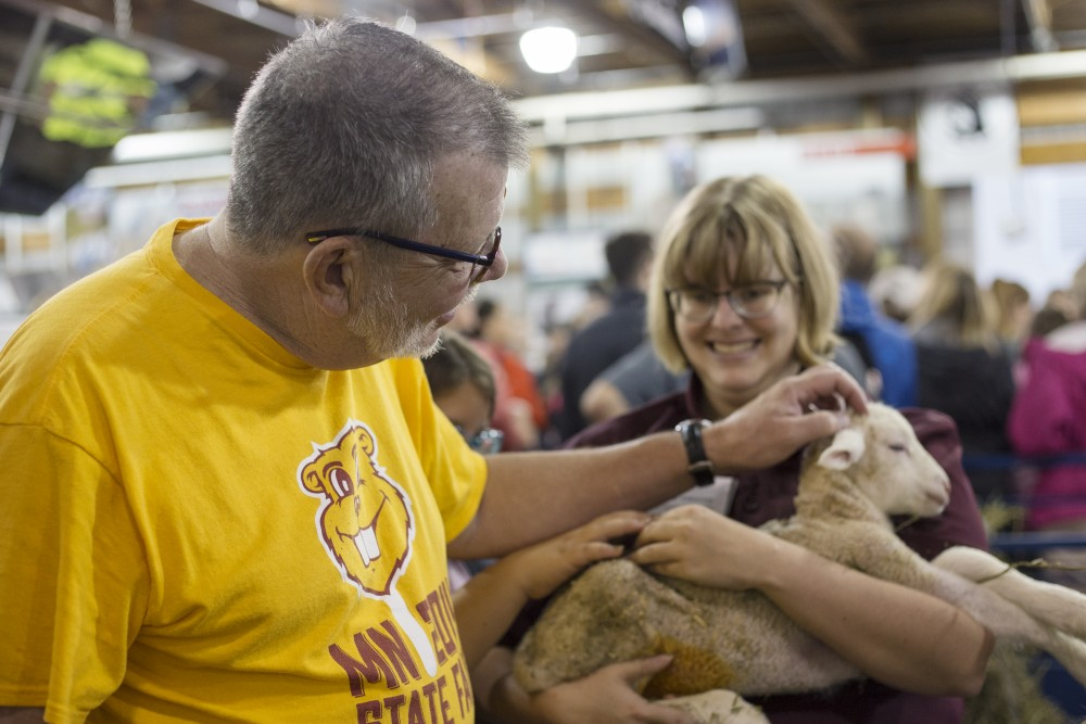President Eric Kaler pets a lamb held by veterinary medicine student Jennifer Pitkanen at the Miracle of Birth Center on Friday, Aug. 24 at the Minnesota State Fair. Kaler spent the day at the fair with his wife.