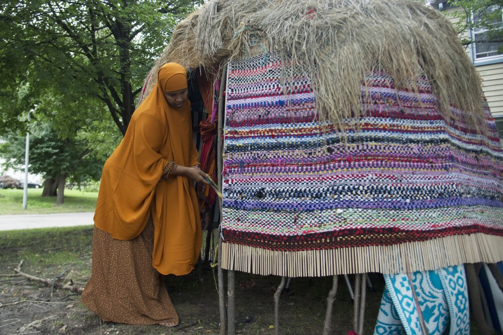 The Somali House, a structure made of sticks and held together by various forms of weaving, is fixed by Cedar Riverside resident Ayan Isaq on Thursday, Sept. 27 in Minneapolis. The house serves as a space for Somali people to gather and experience Somali culture.