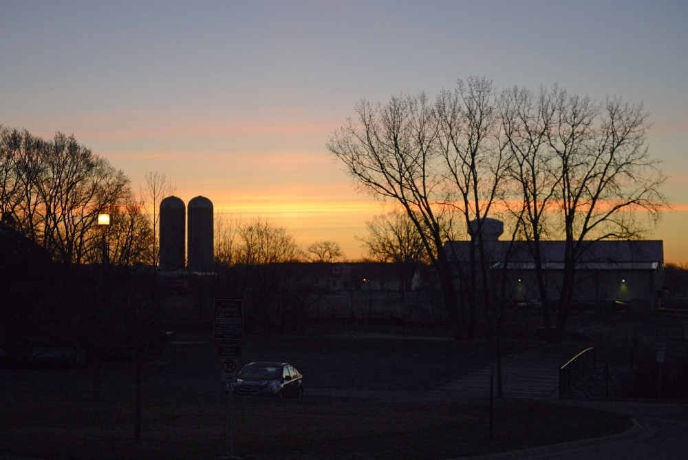 The sun begins to rise over St. Paul campus on April 19, 2017.