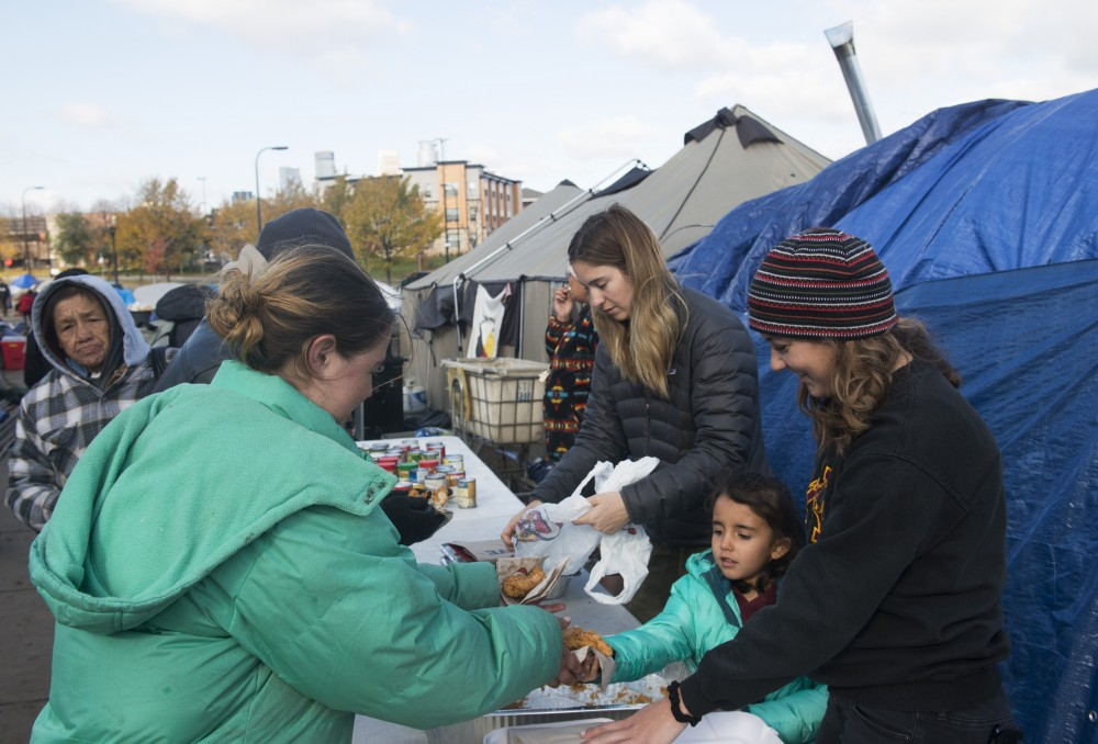 Kristina Tester, right, Marley Molcjan, 5, and Kara Lillehaug hand out food to people on Sunday, Oct. 28 at the homeless encampment in Minneapolis. A large group of homeless individuals has set up tents alongside Hiawatha Avenue.