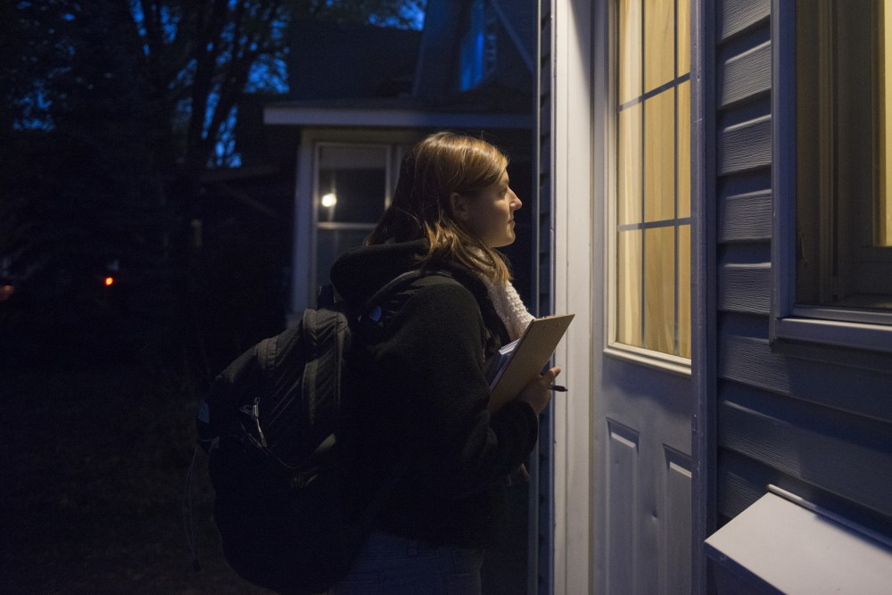Campus Organizer with the DFL Youth-Coordinated Campaign, Michaela Muza, waits for a resident of a Como home to answer the door on Tuesday, Oct. 23 during a door knocking session.