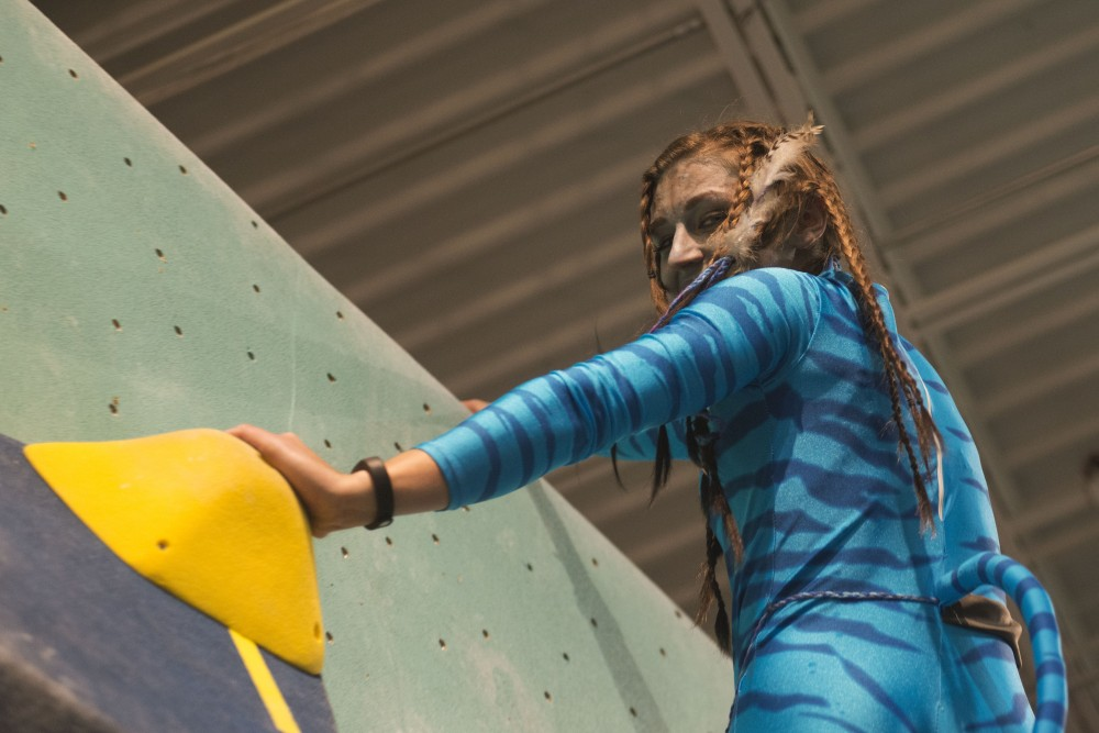Natasha Cramer wears an Avatar costume while they climb at the Minneapolis Bouldering Project on Wednesday, Oct. 31 for a Halloween party.