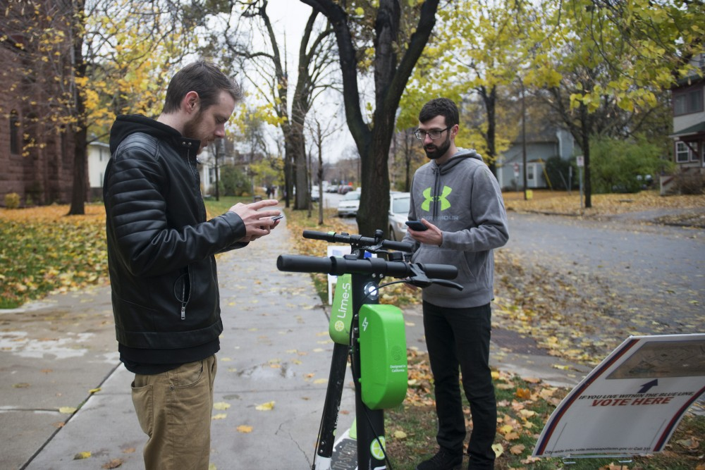 Kevin Walen, left, and Kevin Deitz lock up their Lime scooters before they vote at the First Congregational Church in Marcy-Holmes on Tuesday, Nov. 6.