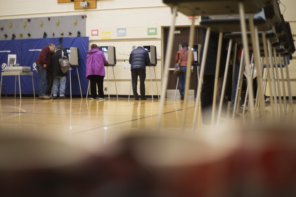Rolls of voting stickers sit on a chair in the foreground while Marcy-Holmes neighborhood residents vote on Tuesday, Nov. 6 at Marcy Open School in Minneapolis.