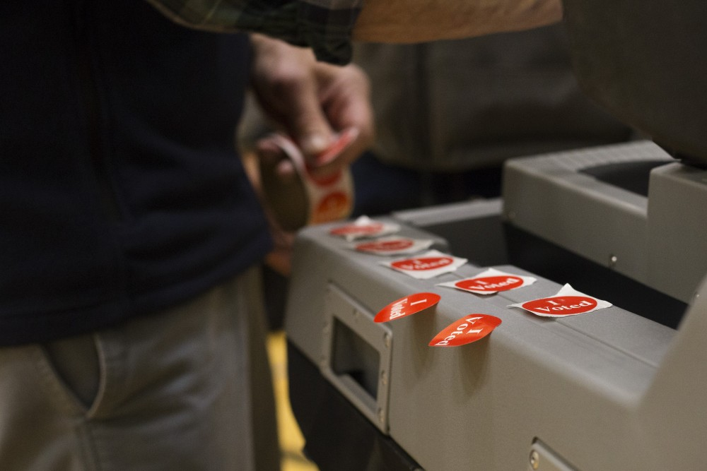 Bob Steller lines up stickers to give out after voters have submitted their ballots on Tuesday, Nov. 6 at Marcy Open School in Minneapolis. Steller has been volunteering at the polls for five or six years as a retirement project.
