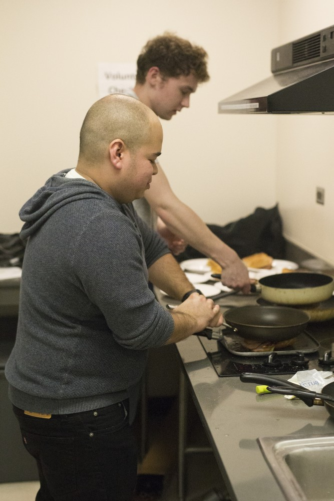 Graduate student Justin Wiese, also the president of the University's Minnesota Cooking Club, presses down on a skillet to finish cooking a cuban club sandwich in the kitchen at Coffman Memorial Union on Wednesday, Nov. 8.