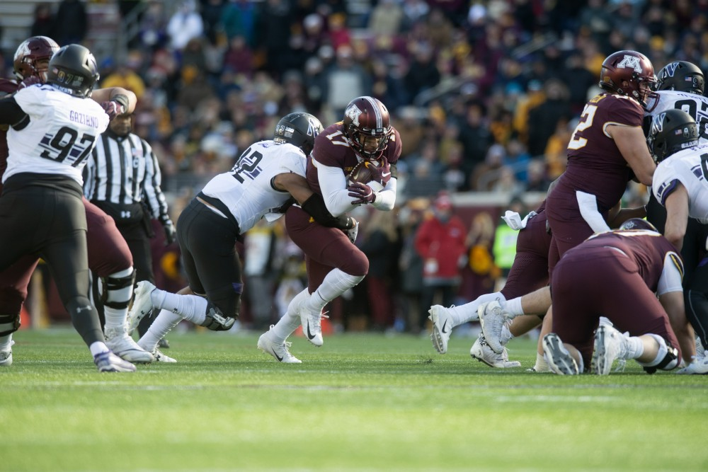 Wide receiver Seth Green fights through a tackle during the game against Northwestern on Saturday, Nov. 17 at TCF Bank Stadium.