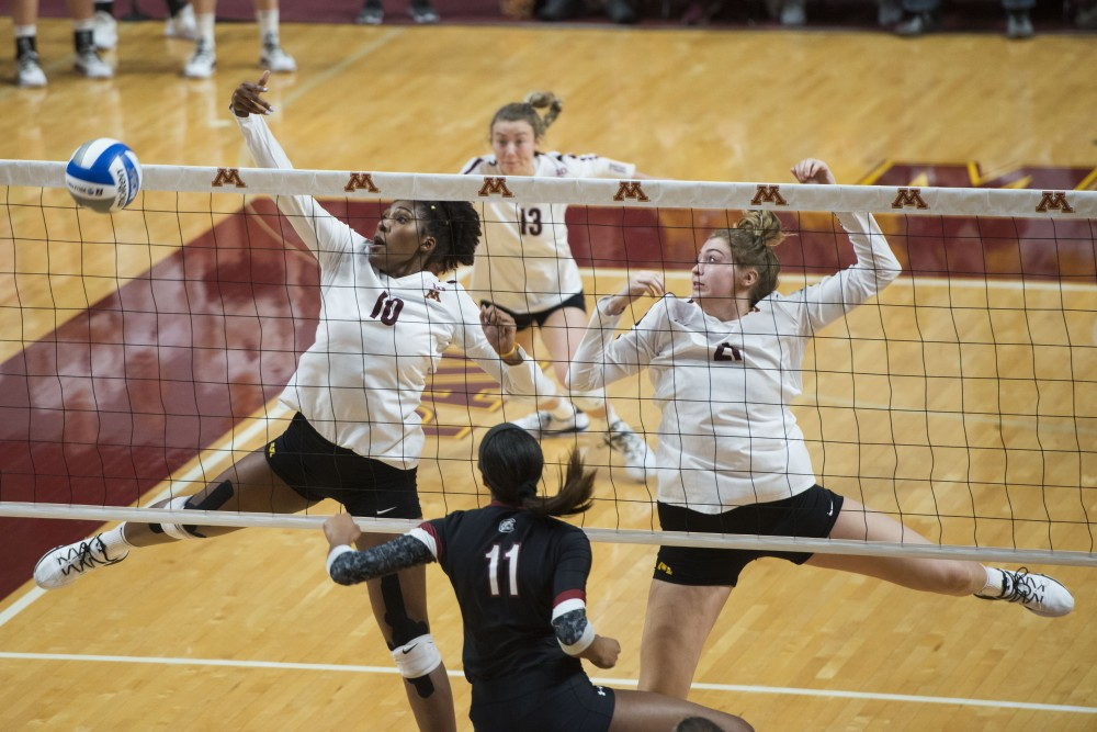 Stephanie Samedy and Regan Pittman block the ball at Maturi Pavilion on Saturday, Dec. 1. The Gophers swept South Carolina in all three sets.