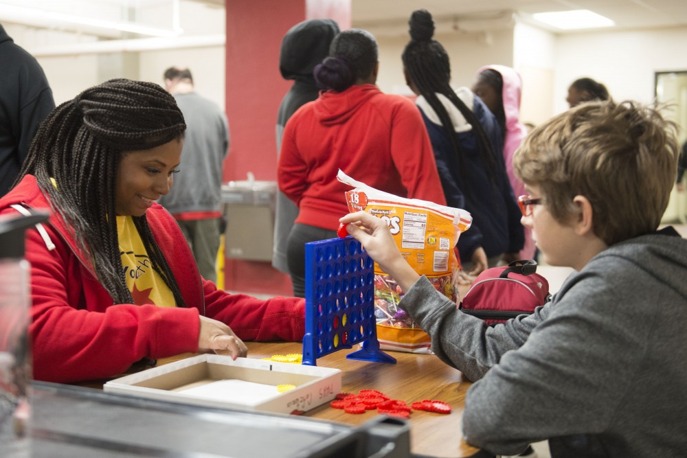 Community Outreach team member Lawanna Pitts plays Connect Four with a student on Friday, Dec. 7 at Patrick Henry High School. YCB Mentors offer guidance to students in areas where structured academics and athletics fall short.