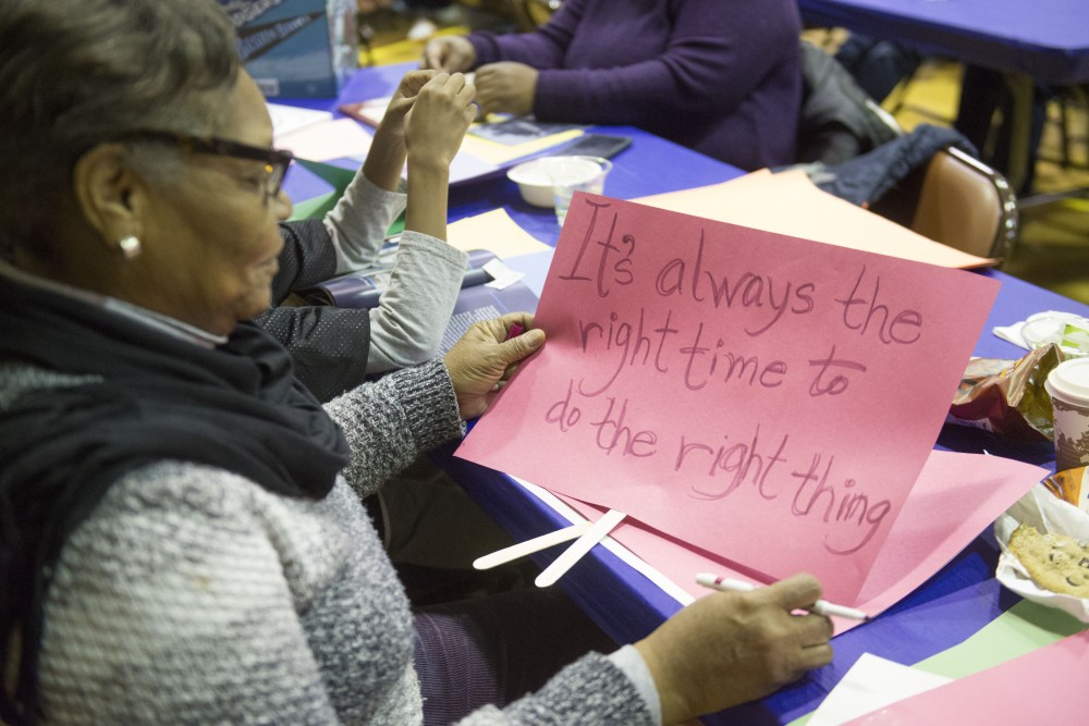 Linda Taylor creates a protest sign on Monday, Jan. 21 at the Powderhorn Recreation Center in Minneapolis. The 21st annual celebration of the Rev. Dr. Martin Luther King Jr., held by the Seward Co-op, drew around 250 people.