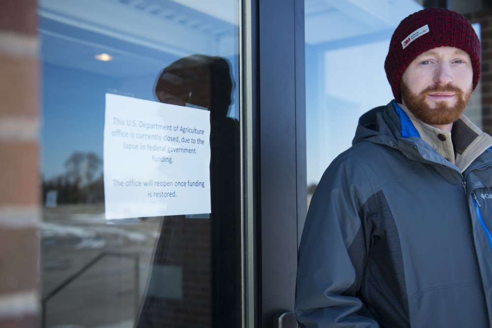 Graduate student Sean O'Mara stands in front of the Cereal Rust Laboratory on Friday, Jan. 25 in St. Paul. The federal government shutdown has caused temporary closure of the lab that O'Mara works in.