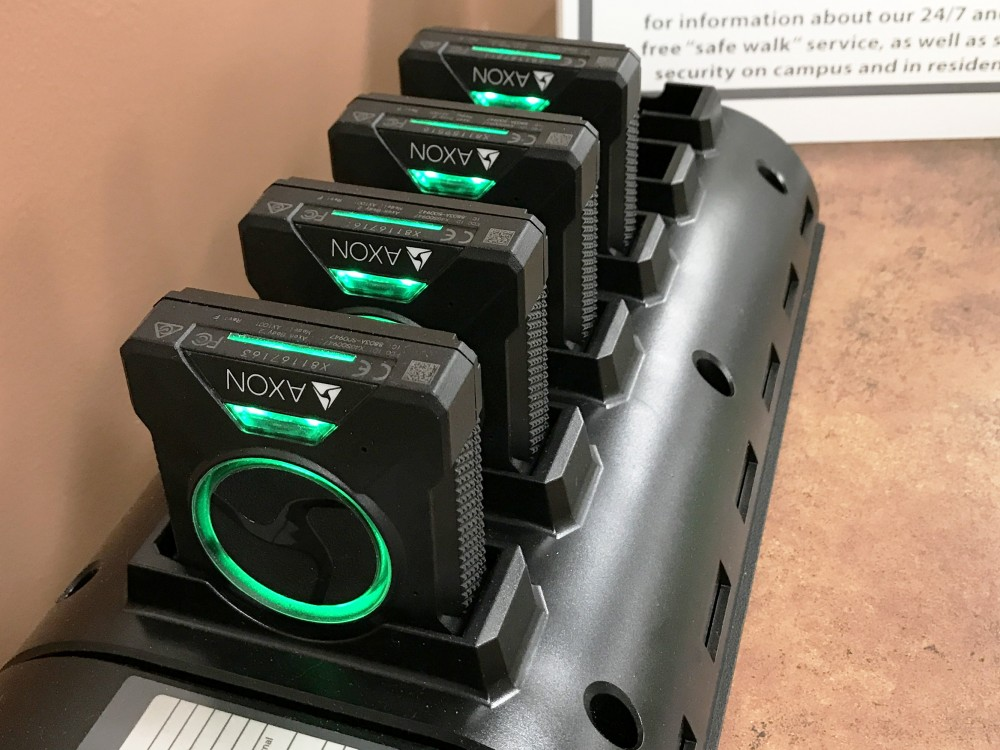 Body cameras sit in a charging cradle.