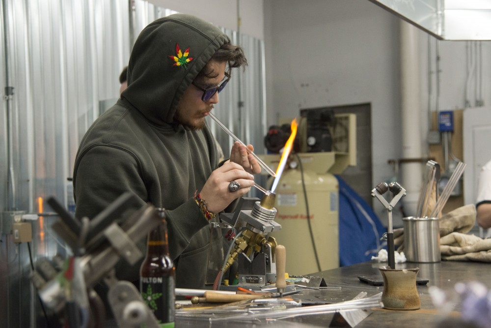 David Rocha works on a glass piece on Saturday, Jan. 26 at Legacy Glassworks in Minneapolis. The show brought together artwork from multiple glasswork and graffiti artists in the Twin Cities.
