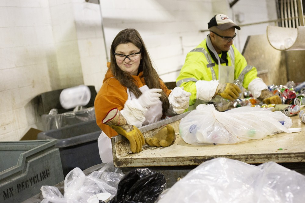 Marissa Calstrom sorts waste into recycling bins at the Como Recycling Facility on Friday, Jan. 18 in Minneapolis. Part of her job is to identify different types of plastic, including what is used for research at the University, and separate them for proper recycling.