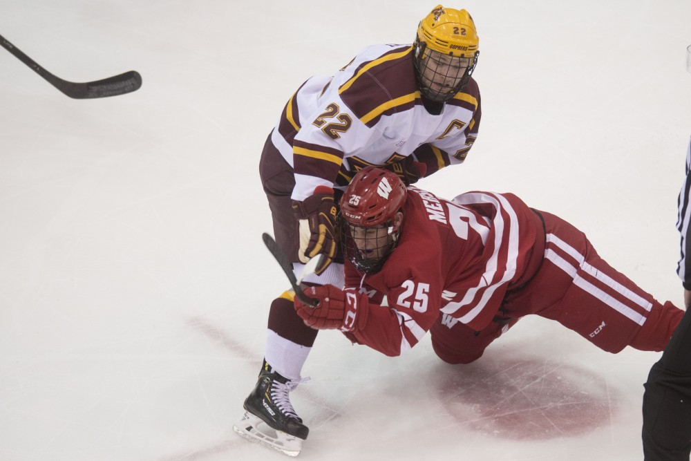 Wisconsin's Dominick Mersch falls into senior Tyler Sheehy at Mariucci Arena on Saturday, Jan 26. The Gophers lost to the Wisconsin Badgers 4-3 after winning 9-4 the night before.