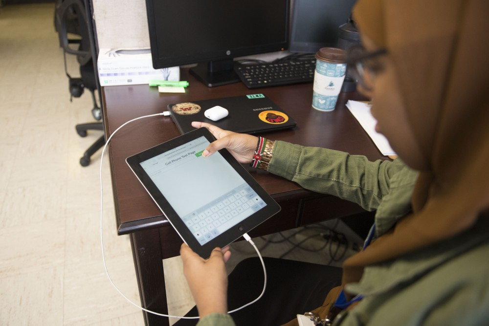 University junior Faisa Ahmed demonstrates how a new health text messaging system, which aims to close the racial gap in healthcare, works on Tuesday, Feb. 5 at the People's Center Clinic in Minneapolis. This system is a research project at the University and is conducting some of the project with families in nearby Cedar-Riverside.
