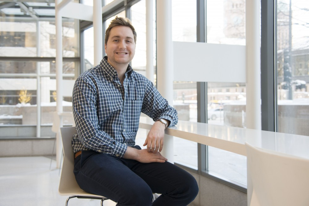 Andrew Swisher, who graduated from the University in 2018, poses for a portrait in downtown Minneapolis on Feb. 8. Swisher created Bibliate, a website that condenses and summarizes scholarly articles that is similar to