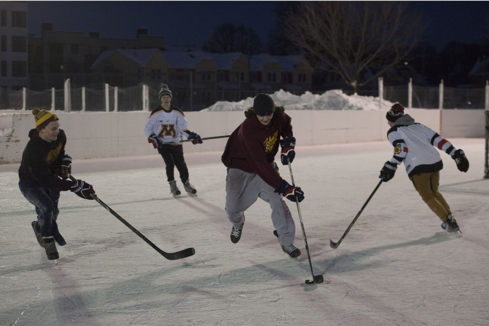 Austin Rush works to keep the puck away from his friends at the Van Cleve Park ice rinks on Wednesday, Feb. 13. The rinks are currently used recreationally and by players who are preparing for the upcoming inter-fraternity