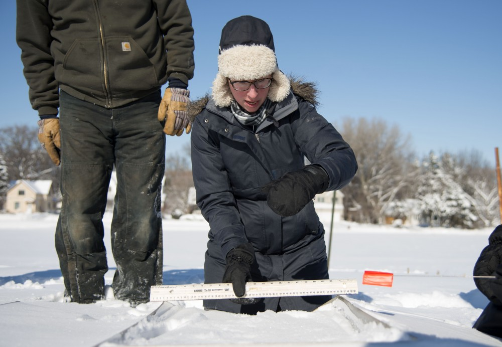 Melissa Wilson measures a plot where manure will be laid on Friday, Feb. 8 in Falcon Heights, Minnesota. Wilson leads several research projects and is currently conducting research to observe manure, snow and its runoff.
