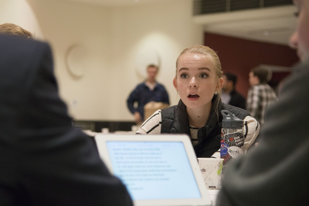 Sophomore Margaux Granath speaks with other MSA members and guest legislators about forum topics at Coffman Union on Tuesday, Dec. 4, 2018.