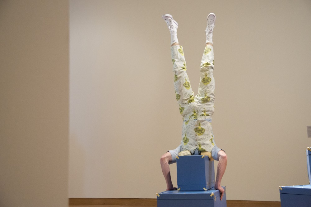 Avery McQuaid Nelson Lawrence does a head stand as part of a performance piece on Friday, Feb. 1 at the new Weisman Art Museum exhibition