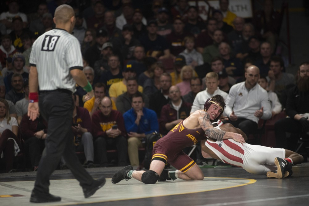Redshirt senior Sean Russell competes against Elijah Oliver of Indiana University on Sunday, March 10 at Williams Arena in Minneapolis. Russell won the match and took third place for the 125 weight class.