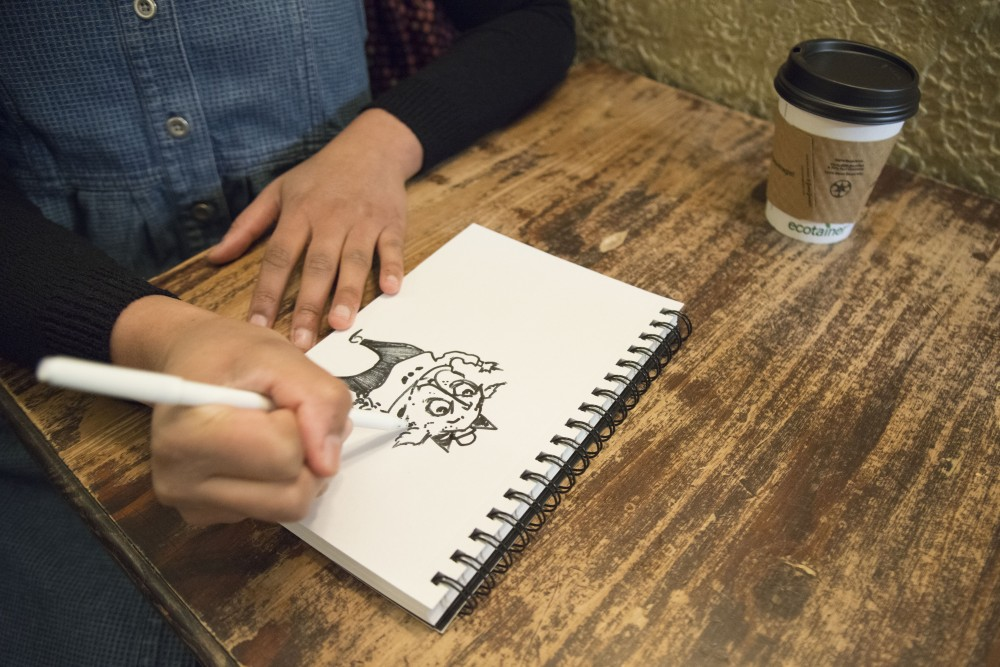 Local illustrator Destiny A. Davison works on a drawing in a new sketchbook on Thursday, March 7 at Bordertown Coffee in Dinkytown.