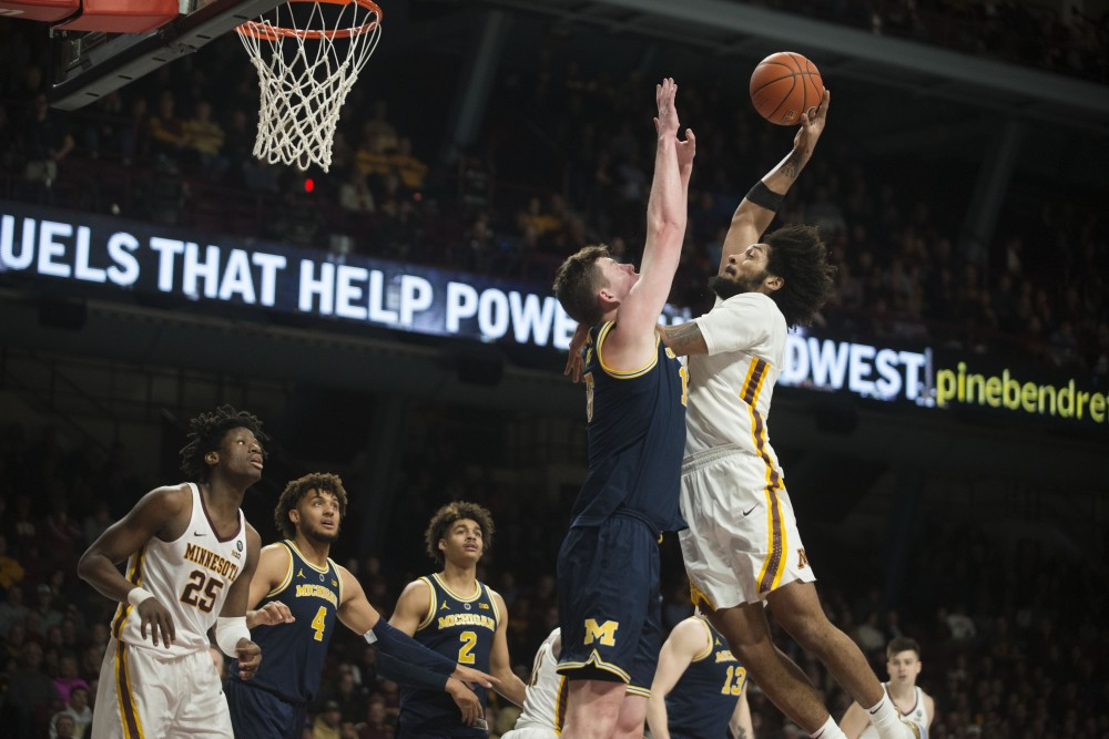 <p>Senior Jordan Murphy jumps to dunk the ball on Thursday, Feb. 21 at Williams Arena in Minneapolis. The Gophers lost to Michigan 69-60.</p>