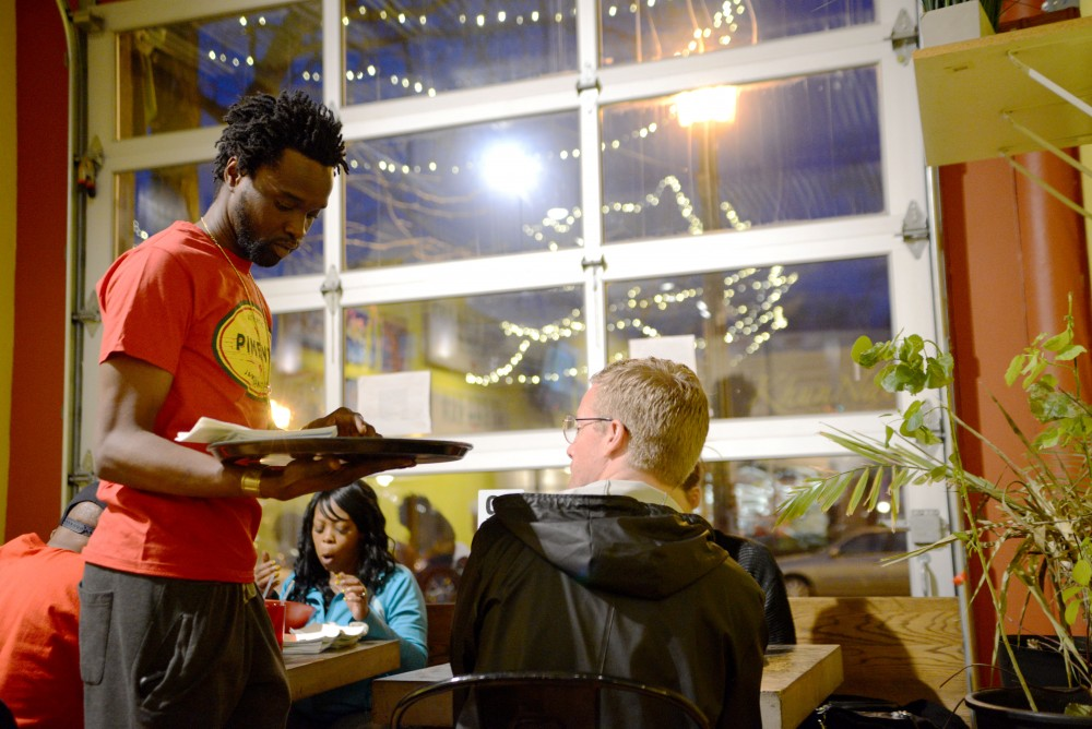 Kemar Edwards serves food to customers on Saturday, March 23 at Pimento Jamaican Kitchen in Minneapolis. The restaurant was celebrating 3 years of being in Minneapolis on Saturday night.