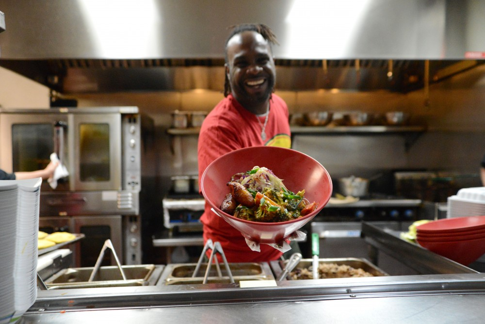 Pimento owner Tomme Beevas poses for a portrait with a dish on Saturday, March 23 at Pimento Jamaican Kitchen in Minneapolis. The restaurant was celebrating 3 years of living in its space on Eat Street.