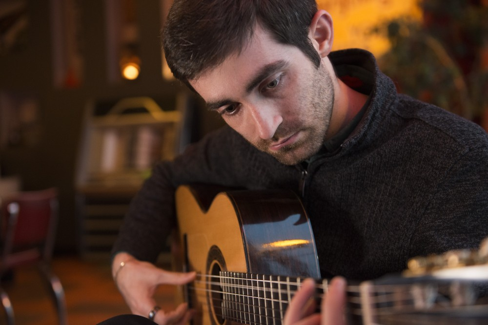 Daniel Volovets, a medical student at the University, plays his guitar in The Bad Waitress in South Minneapolis on Friday, Mar. 1.