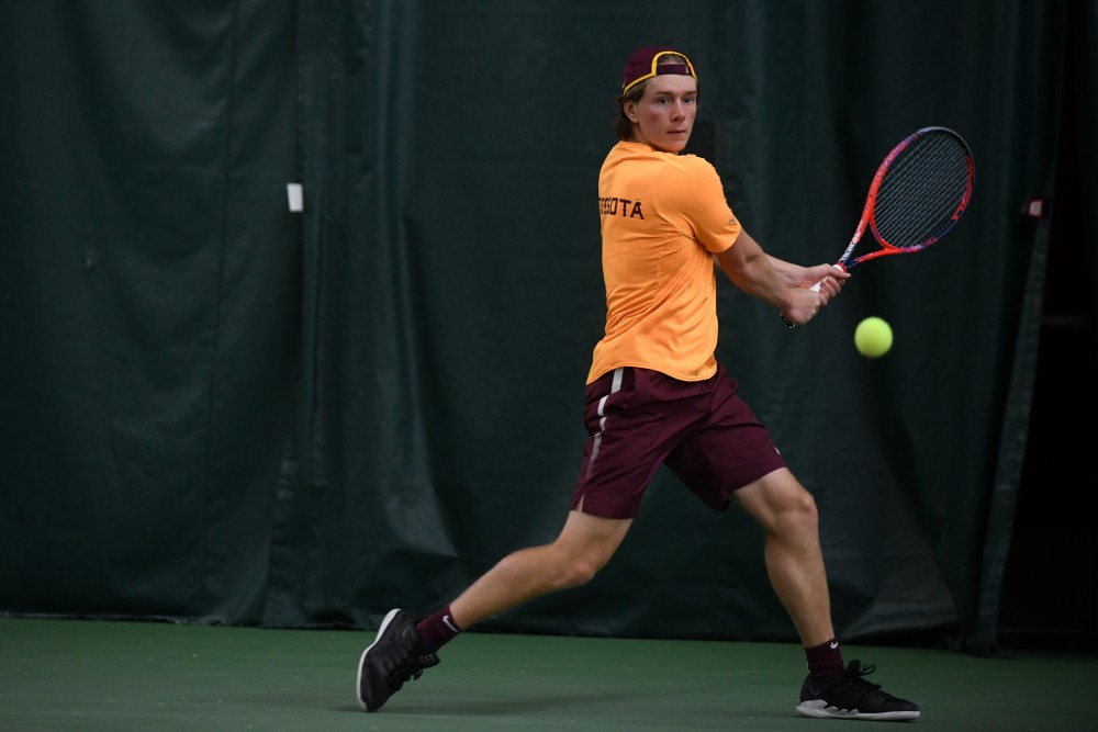 Junior Eli Ogilvy returns the ball on Friday, March 22 at the Baseline Tennis Center.