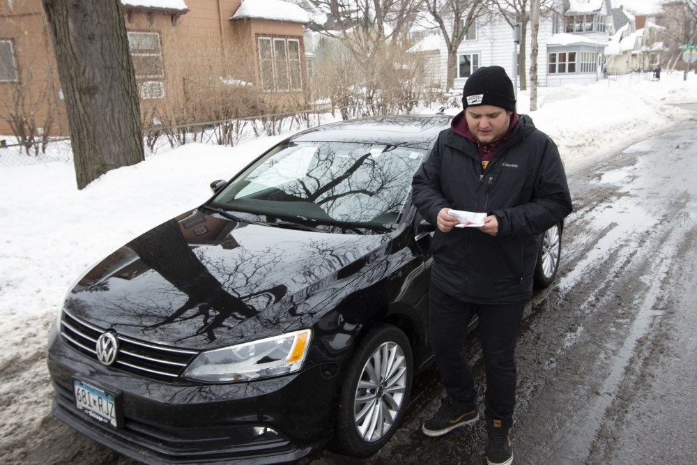 Cameron Eller removes a parking ticket he got after being confused about where he should park because of Minneapolis' winter parking restrictions on Saturday, March 9, 2019. Eller received the ticket a day before, but had been leaving it on his car for